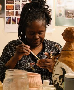 A black woman artist, Christine Bethea paints her ceramic work with her turned down slightly.