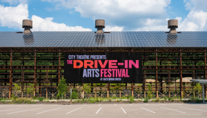 """Large black billboard with bright pink and lavender letters that say """"City Theater Presents The Drive-In Arts Festival"""" outside of Hazelwood Green"""