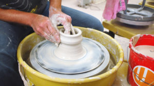 Close up of hands on shaping a white clay body spinning on a wheel.