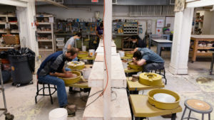 Long view of wheel area of the studio with several students leaning over their projects as they work on them, while wearing masks.