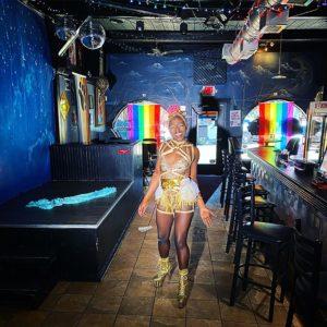 Black drag queen Luna Plexus in bright gold costume smiling inside Blue Moon