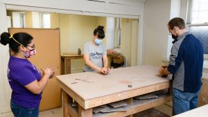 Three people wearing masks standing around a studio table working on individual pieces of clay with their hands.