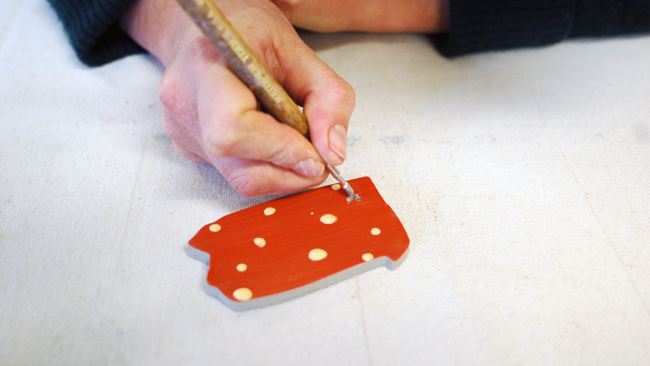 White hand holding a carving tool over a clay piece colored red with white dots, in the shape of the state of Pennsylvania.