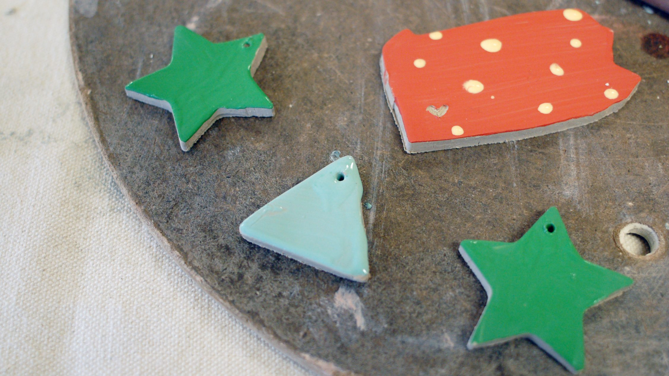 Close-up of four ceramic ornaments in progress: 2 green stars, one blue triangle, and a red with white dots ornament shaped like the state of Pennsylvania.