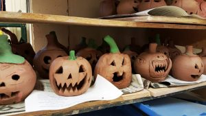 Wooden shelving with several partially dried clay pumpkins carved into Jack-o-Lanterns. The stems are painted green.