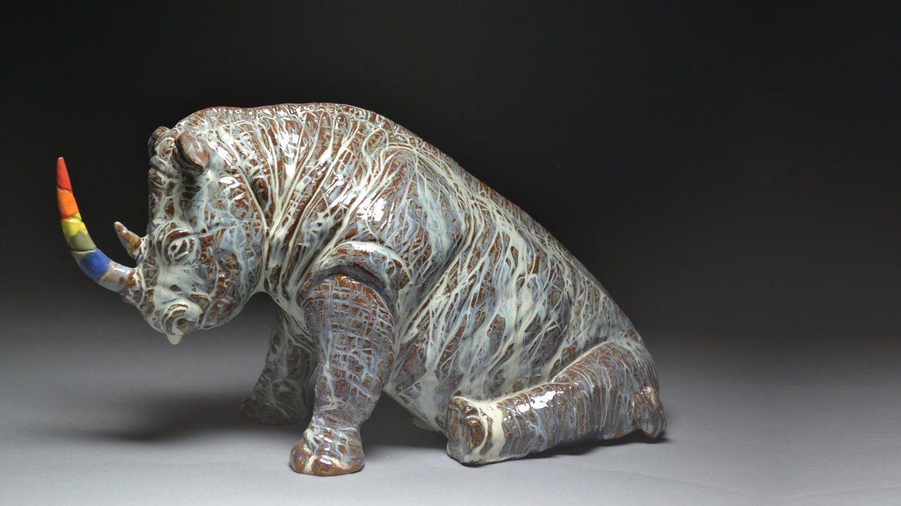 Ceramic rhinoceros with grey textured skin and rainbow horn, by Mac McCusker.